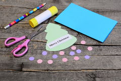 Fazendo um cartão do Natal etapa Árvore de Natal e corte dos ornamento das bolas do papel colorido, lápis, vara da colagem, tesou Imagens de Stock