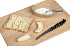 Fazendo um sanduíche da banana e do açúcar em uma placa de desbastamento Imagens de Stock Royalty Free