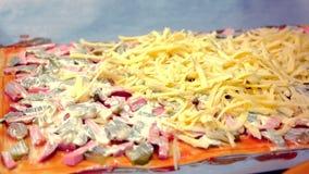 Fazendo uma pizza caseiro O homem põe um queijo sobre a massa com ingredientes, mão do close-up vídeos de arquivo