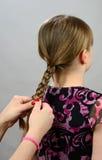 Fazendo uma trança do cabelo para a menina Foto de Stock