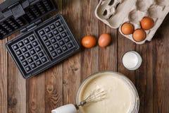 Fazendo waffles em casa - ferro de waffle, massa na bacia e ingredientes - leite e ovos Fotografia de Stock Royalty Free