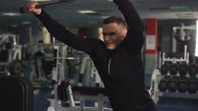 Fazer atl?tico novo do homem puxa para baixo o exerc?cio para o tr?ceps no gym video estoque