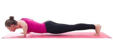 Fazer bonito da mulher levanta o exercício na esteira da ioga isolada em w fotos de stock royalty free