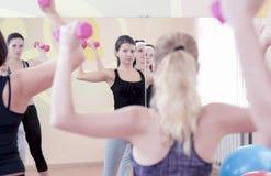 Fazer caucasiano atlético de quatro mulheres dá certo exercícios com os Barbells no Gym fotos de stock
