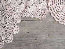 Fazer crochê doilies sobre a madeira cinzenta velha Fotografia de Stock Royalty Free