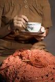 Fazer crochê e as mãos do ` s da mulher com copo de chá O conceito dos passatempos e do lazer Imagens de Stock Royalty Free