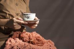 Fazer crochê e as mãos do ` s da mulher com copo de chá O conceito dos passatempos e do lazer Imagem de Stock Royalty Free