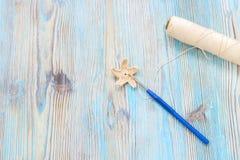 Fazer crochê a estrela feito a mão, bola bege do fio de algodão e fazer crochê o gancho do metal na tabela de madeira Fotografia de Stock