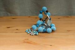 Fazer crochê grânulos azuis feitos a mão e um espelho de mão Imagens de Stock Royalty Free