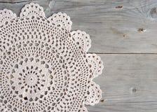 Fazer crochê o doily sobre a madeira cinzenta velha Imagem de Stock Royalty Free