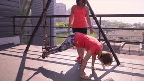 Fazer da menina investe contra com pesos A menina faz ataques no gym em um terassa da rua vídeos de arquivo