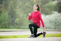 Fazer desportivo da mulher investe contra exercícios antes de correr fotos de stock