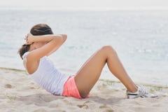 Fazer desportivo da mulher senta-se acima na praia fotografia de stock