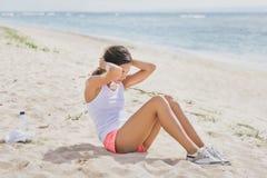 Fazer desportivo da mulher senta-se acima na praia imagem de stock