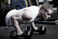 Fazer do homem da foto empurra manter o peso no gym Fotos de Stock