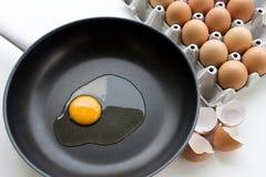 Fazer eggs em uma caçarola e em uma bandeja de ovos crus Foto de Stock