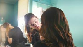 Fazer fêmea do estilista profissional compensa pela jovem mulher na frente do espelho no salão de beleza vídeos de arquivo