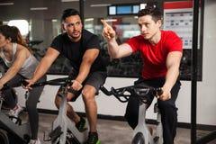 Fazer masculino dos amigos cardio- em uma bicicleta Fotografia de Stock