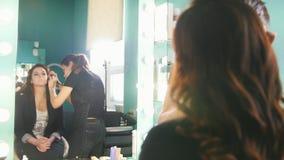 Fazer profissional do estilista compensa pela jovem mulher no salão de beleza video estoque