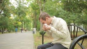 Fazzoletto della tenuta del giovane sul naso un uomo ha un cattivo freddo stock footage