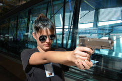 FBI woman agent. A woman, a FBI agent, points her weapon at a target situated beyond the image stock images