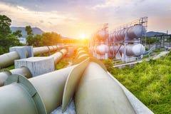 Fábrica de la refinería de la industria del petróleo y gas en la puesta del sol Imágenes de archivo libres de regalías