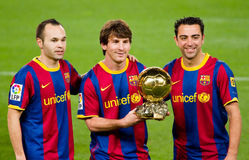 FC Barcelona Golden Ball Trophy. BARCELONA - JANUARY 12: Iniesta, Messi and Xavi offering the FIFA World Player Gold Ball Award to the soccer supporters of Stock Photos