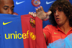 FCB Unicef Jersey. Thierry Henry and Carles Puyol hold up FC Barcelona 2008/2009 jersey.  The club proudly sponsors UNICEF Stock Images