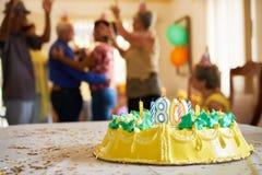 Födelsedagparti för beröm 80 med lyckligt äldre folk i Hospi Royaltyfri Foto