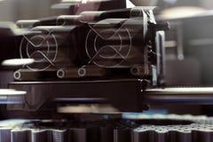 FDM 3D打印机制造业从银灰色细丝的正齿轮在方案磁带-在移动的打印头和喷管的正面图上 库存图片
