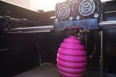 FDM 3D打印机制造业使桃红色复活节彩蛋雕塑-在对象、打印头和机器房间的广角看法受伤 库存照片
