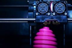 FDM 3D打印机制造业使桃红色复活节彩蛋雕塑-在对象和打印头的正面图受伤 库存图片