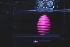 FDM 3D打印机制造业使桃红色复活节彩蛋雕塑-在对象和打印头的正面图受伤 免版税库存图片