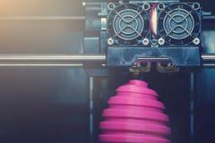 FDM 3D打印机制造业使桃红色复活节彩蛋雕塑-在对象和打印头的正面图受伤 免版税库存照片