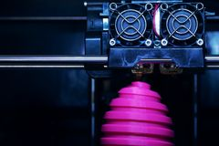 FDM 3D-printer manufacturing wound pink easter egg sculpture - front view on object and print head stock images