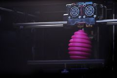 FDM 3D-printer manufacturing wound pink easter egg sculpture - front view on object and print head royalty free stock image