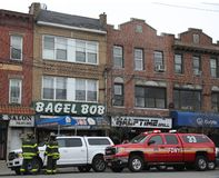 FDNY引擎和消防队员在被烧的企业前面在5警报火烧伤企业以后在布鲁克林,纽约 库存图片