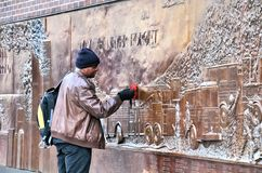 The FDNY 9.11.01 Memorial Wall. Man cleaning the bronze wall of the FDNY Memorial Wall, where are engraved the 343 names of the firefighters that perished on Stock Image