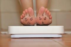 Füße auf Badezimmerwaage Stockfoto