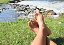 Füße auf Gras durch Wehr Stockfotografie