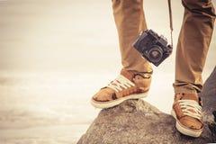 Füße bemannen und die Retro- Fotokamera der Weinlese im Freien Stockfotografie