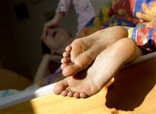 Füße der Frau im Bett Lizenzfreie Stockbilder
