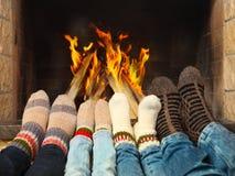 Füße, die nahe dem Kamin sich wärmen Stockbilder