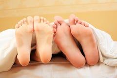 Füße in einem Bett Stockfoto
