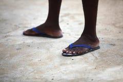 Füße eines afrikanischen Mannes in den blauen Flipflops Stockfotos