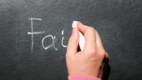 Fe - la mano escribe palabra en concepto de la pizarra, de la religión y del cristianismo metrajes