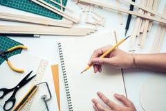 Feale travaillant à la table de travail avec le matériel en bois de balsa Diy, projet de conception photographie stock
