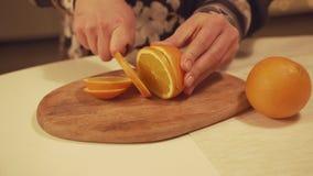 Feamale-Hände, die Orange auf Schneidebrett für selbst gemachten Glühwein mit orange Scheiben, Moosbeeren, Zimt schneiden stock video footage