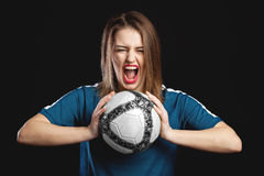 Feamel soccer player screaming with soccer ball in hands Stock Photos