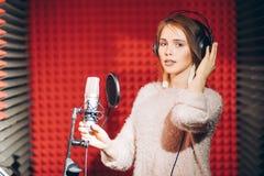 Feamle louro na roupa da forma que levanta à câmera ao cantar no estúdio foto de stock royalty free